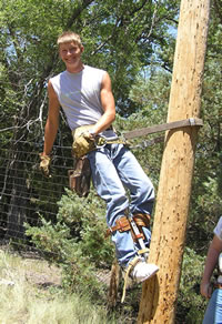 Student on electric pole at Youth Energy Camp